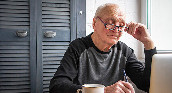 Elderly man ready emails on laptop