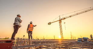 Two construction employees surveying a building site