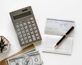Calculator, money and a pen