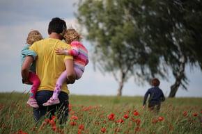 Man carrying two kids in open field