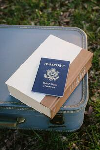 Passport on top of Book and Luggage
